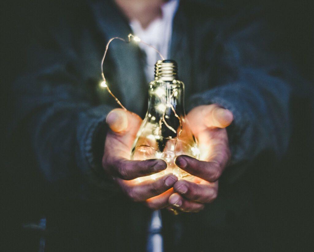 offene Hände mit leuchtender Glühlampe