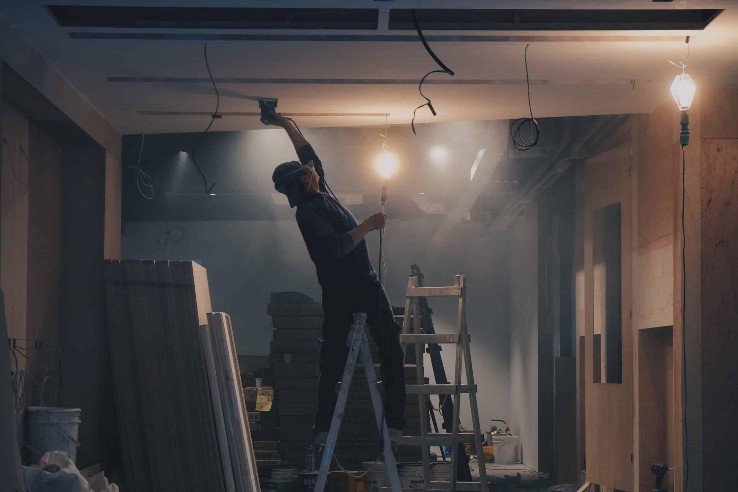 Handwerker arbeitet auf einer Leiter , schleift die Rohdecke